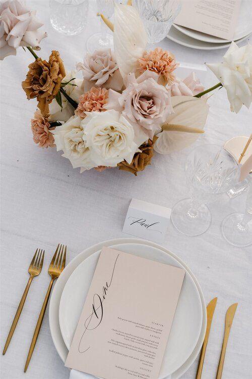 In questa foto una mise en place minimal chic con tovaglia in lino bianca, posate colore oro, piatti bianchi e bicchieri di cristallo. Sul piatto è appoggiato il menù color cipria. Il centrotavola è realizzato con rosa bianche, rosa e bronzo