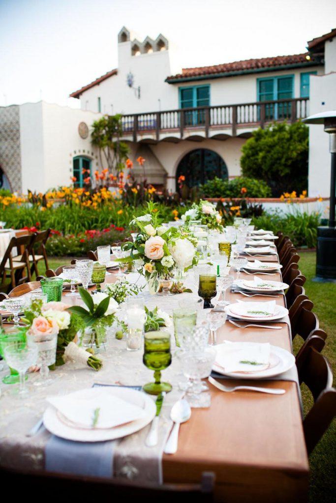 In questa foto un ricevimento di nozze allestito su un prato fiorito di un casale. Su due tavoli imperiali in legno è usato un runner di pizzo al posto di una tovaglia, i piatti sono bianchi abbinati a bicchieri verde bosco. I centrotavola sono piccoli vasetti di rose bianchi e rosa