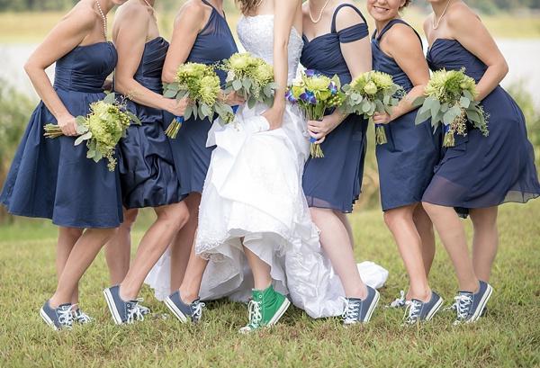 In questa foto una sposa con  Converse verdi posa con le sue sei damigelle vestite di blu scuro e Converse in coordinato. Tra le mani tengono tutte un bouquet di fiori verdi e blu