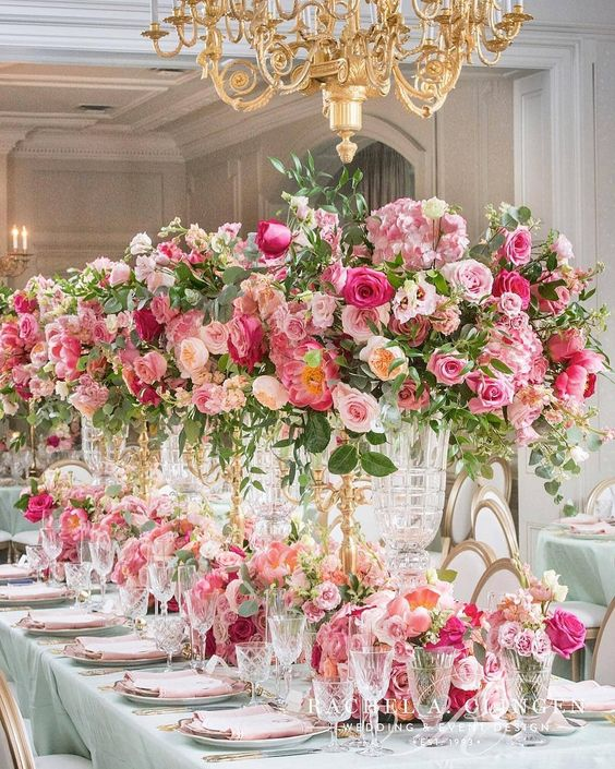 In questa foto un allestimento di matrimonio in una sala elegante. Il tovagliato è colore Tiffany e rosa cipria. I centrotavola sono realizzati con candelabri colore oro decorati con rose rosa e fuxia, ortensie rosa e foglie. Completano la decorazione un runner di fiori in coordinato