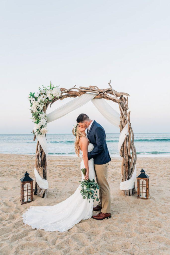 In questa foto due sposi si baciano dopo essersi scambiate le promesse sulla spiaggia davanti ad un arco di legno decorato con fiori bianchi e lanterne in coordinato. La sposa porta tra i capelli una piccola corona di fiori e foglie