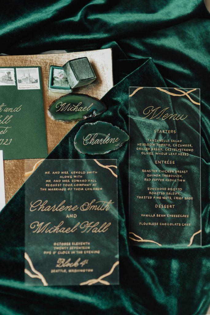 In questa foto una wedding stationery, cioè il coordinato cartaceo di un matrimonio, colore smeraldo. La partecipazione e il menù sono stampati su carta plastificata e trasparente con caratteri e decorazioni oro