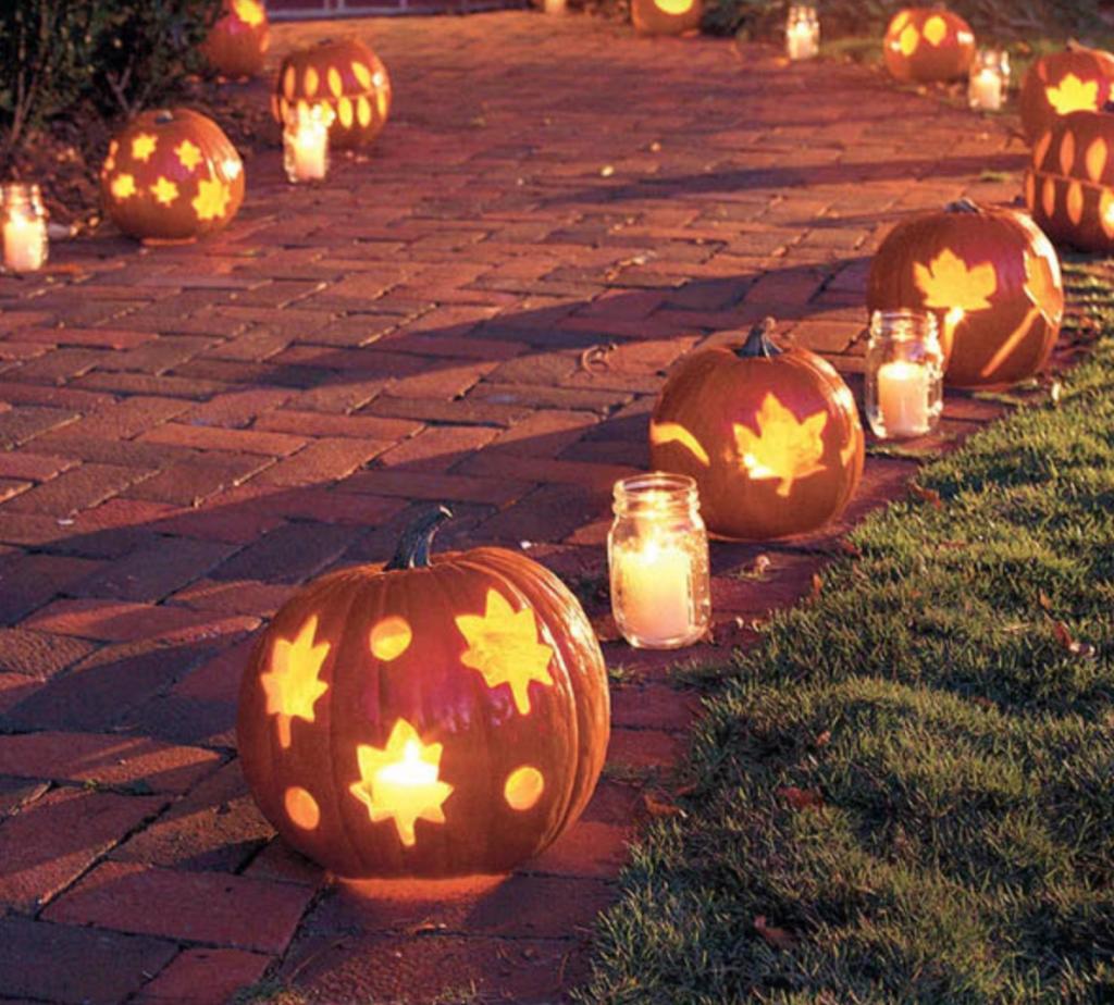 In questa foto un vialetto decorato con lanterne di zucche e vasette con candele bianche, decorazioni perfette per un matrimonio a tema Halloween