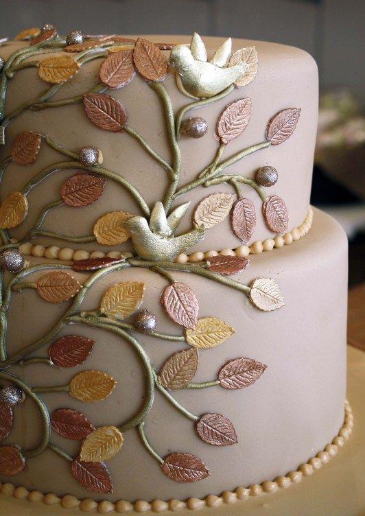 In questa foto una torta nuziale a tema albero della vita nel colore cipria. È decorata con rami e foglioline di pasta di zucchero nei colori oro e bronzo