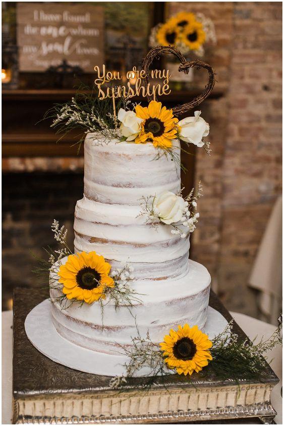 """In questa foto una naked cake per un matrimonio a tema girasoli adagiati sui tre piani insieme a boccioli di rosa bianchi e a fiori velo di sposa. Il cake topper dice """"You are my sunshine"""" cioè """"Sei la mia luce del sole"""""""
