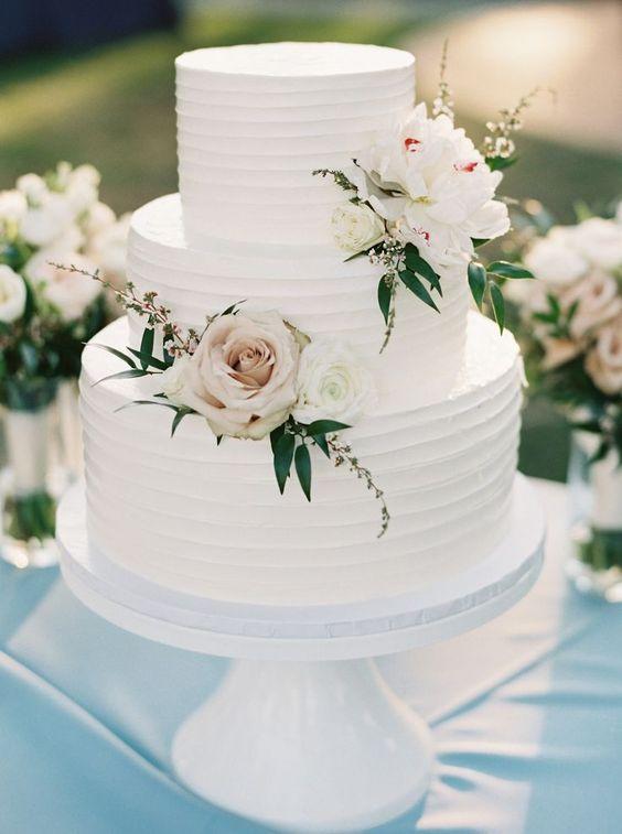 In questa foto una torta nuziale a tre piani decorata con panna e rose bianche, perfetta per un matrimonio classico ed elegante