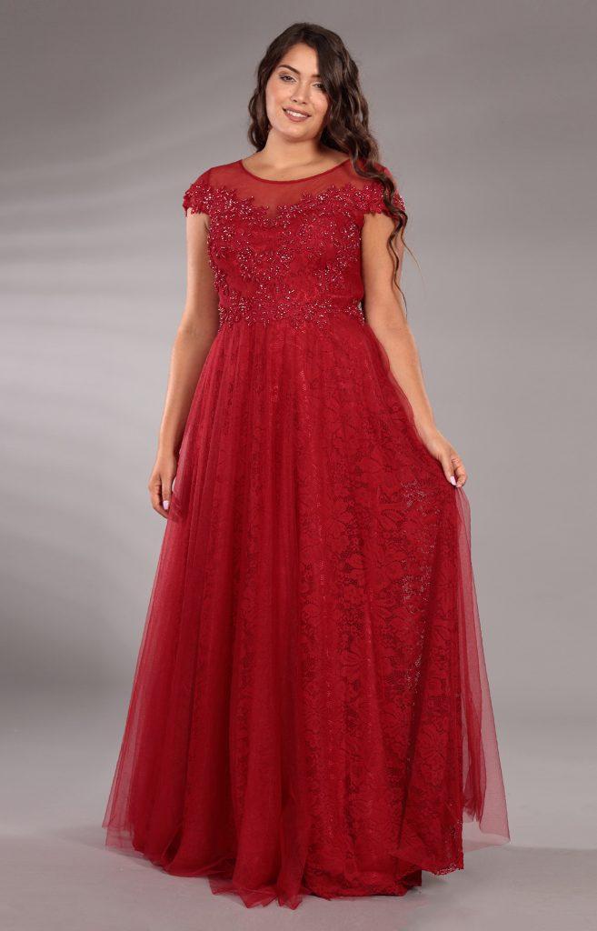 In questa immagine un abito da cerimonia rosso con corpetto ricoperto di dettagli preziosi e gonna in pizzo