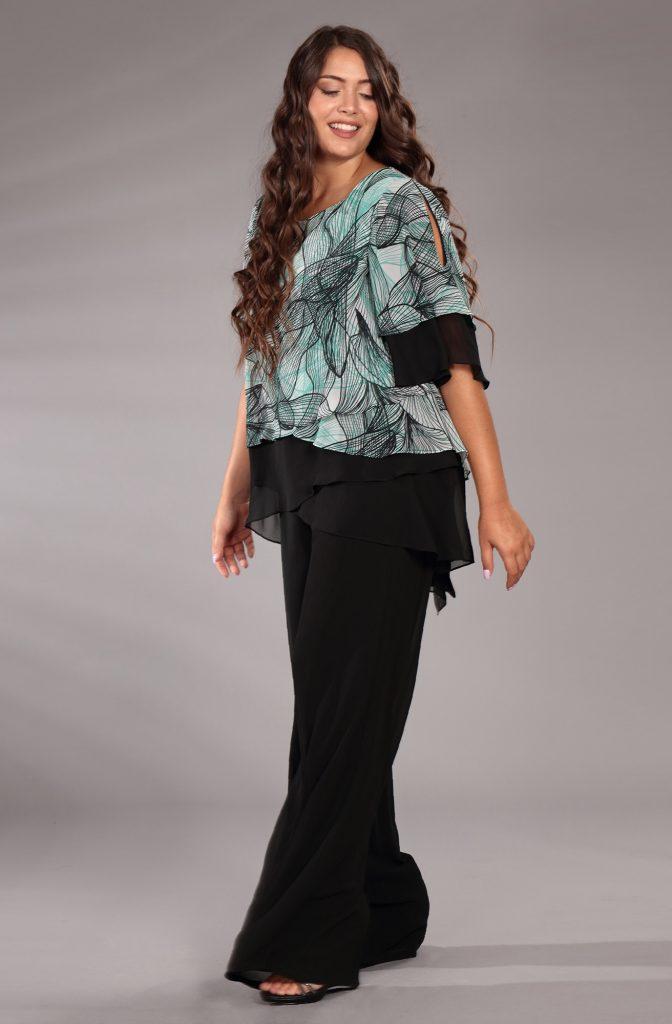 In questa immagine un modello con blusa a fiori e pantalone nero