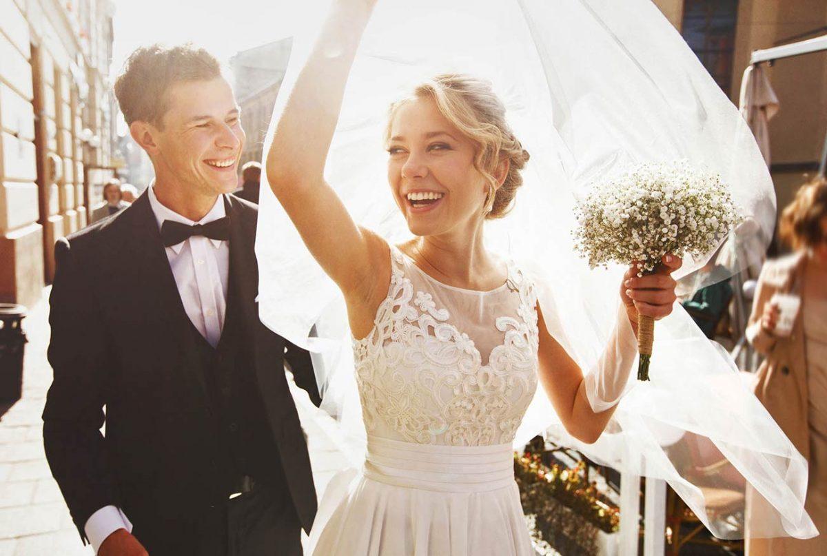 In questa foto due sposi corrono sorridenti sollevando il velo della sposa