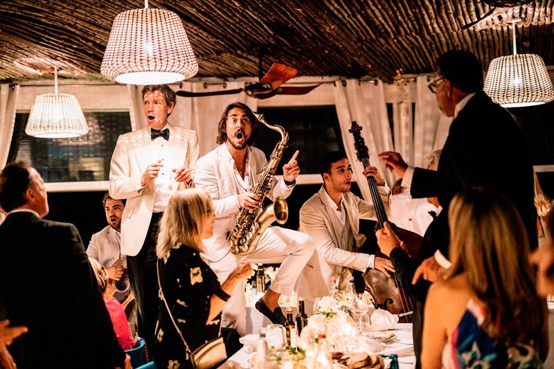 In questa foto un musicista che suona il sax balla e si diverte con gli ospiti di un matrimonio