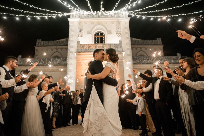 In questa foto due sposi abbracciati, intenti a guardarsi negli occhi, mentre sono circondati dagli invitati del loro matrimonio