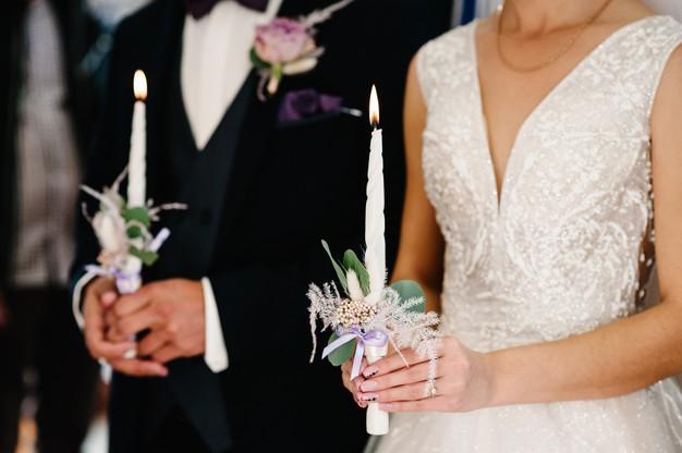 In questa foto due sposi tengono nelle loro mani due candele durante il rito simbolico di un matrimonio civile
