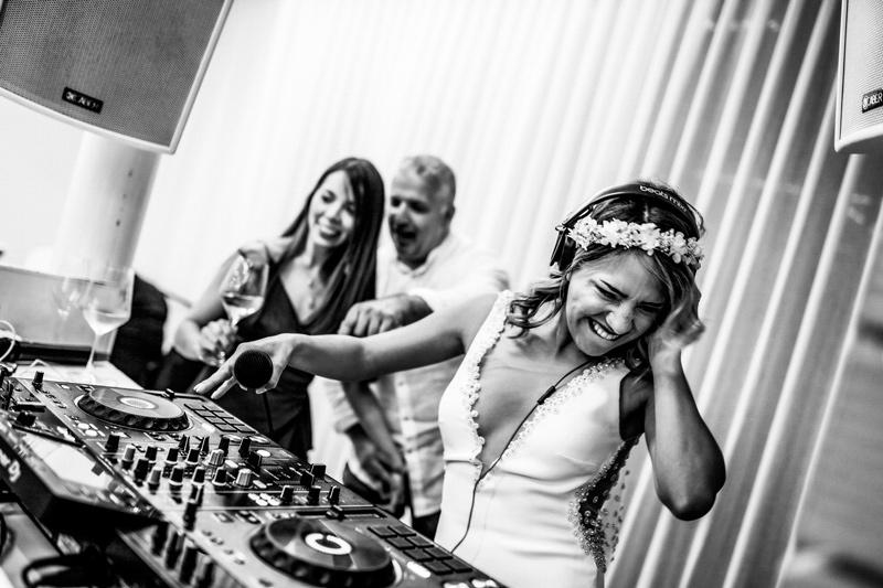 In questa foto una sposa alla console del dj mentre passa musica per il suo matrimonio