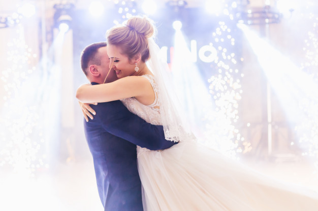 In questa foto due sposi abbracciati sulla pista da ballo del loro ricevimento nuziale