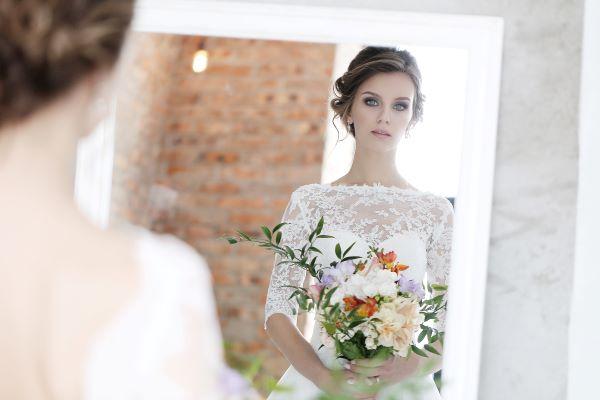In questa foto una sposa mentre si guarda allo specchio con in mano il suo bouquet
