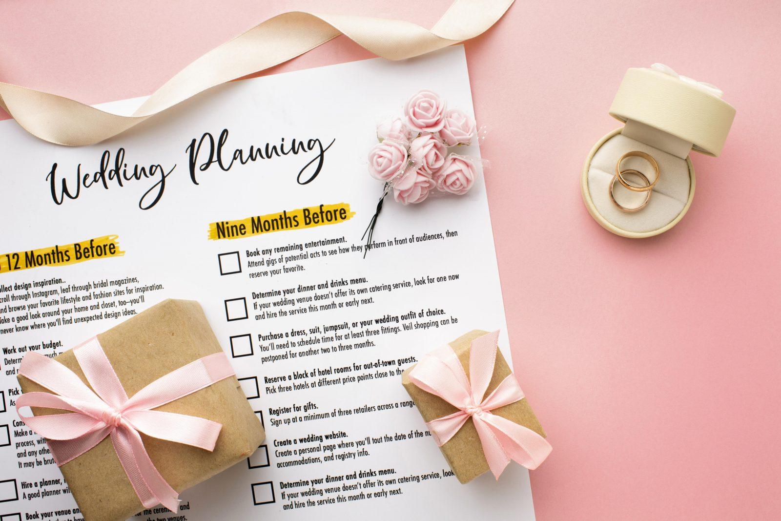 In questa foto il calendario di un wedding planner su sfondo rosa e piccole scatole in cartoncino