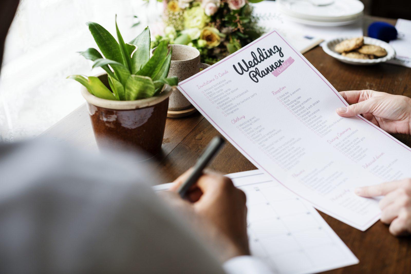 In questa foto un wedding planner tiene in mano una scheda per organizzare un matrimonio