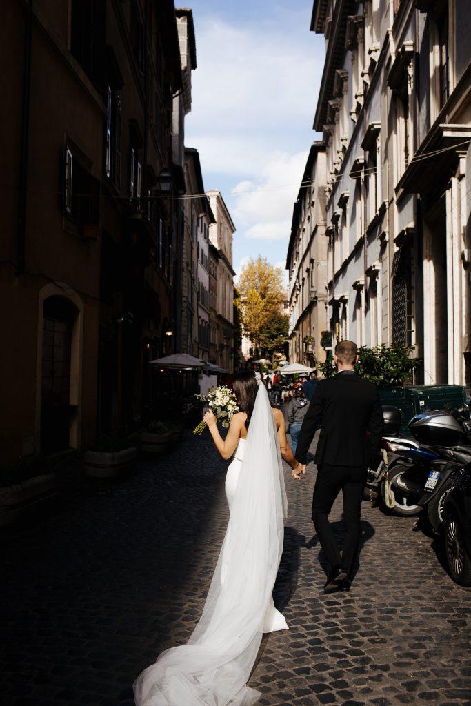 In questa foto una coppia di sposi ripresa di spalle, mentre cammina per le strade di Roma