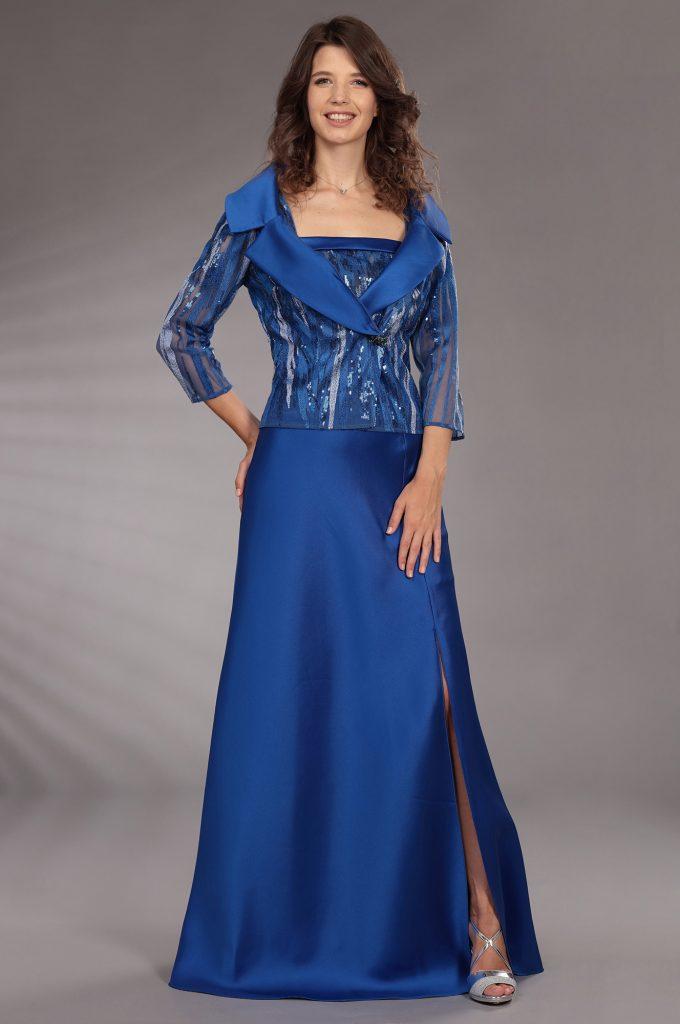 In questa immagine un lungo e fluido abito della maison italiana. con giacca blu.