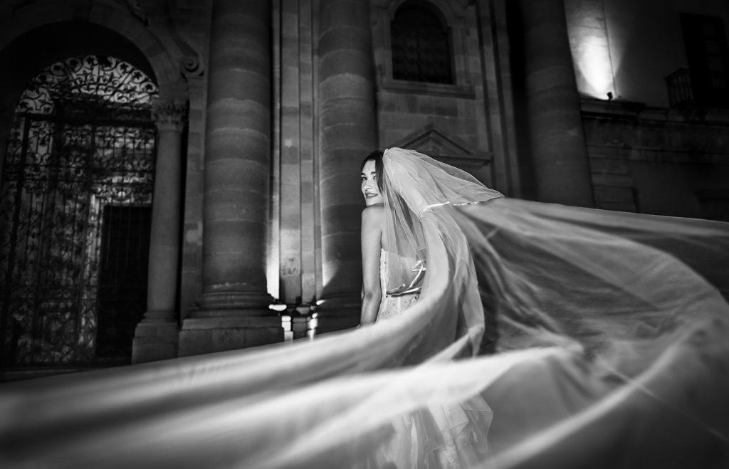 In questa foto di Andrea Finos wedding&portraits in primo piano il lungo velo della sposa