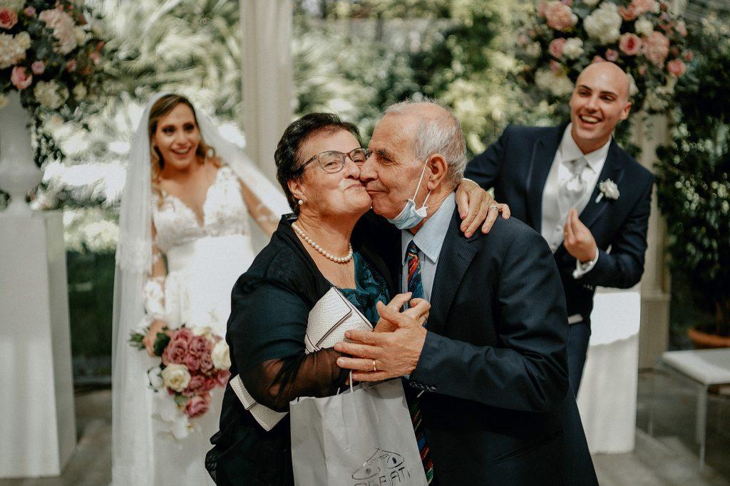 In questa foto di Belvedere Fotografi una coppia di invitati si bacia davanti agli sposi