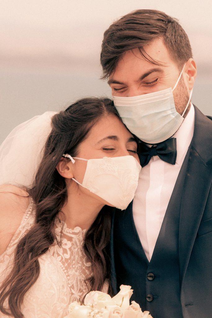 In questa foto di Costanzo D'Angelo gli sposi ridono felicemente sotto le mascherine