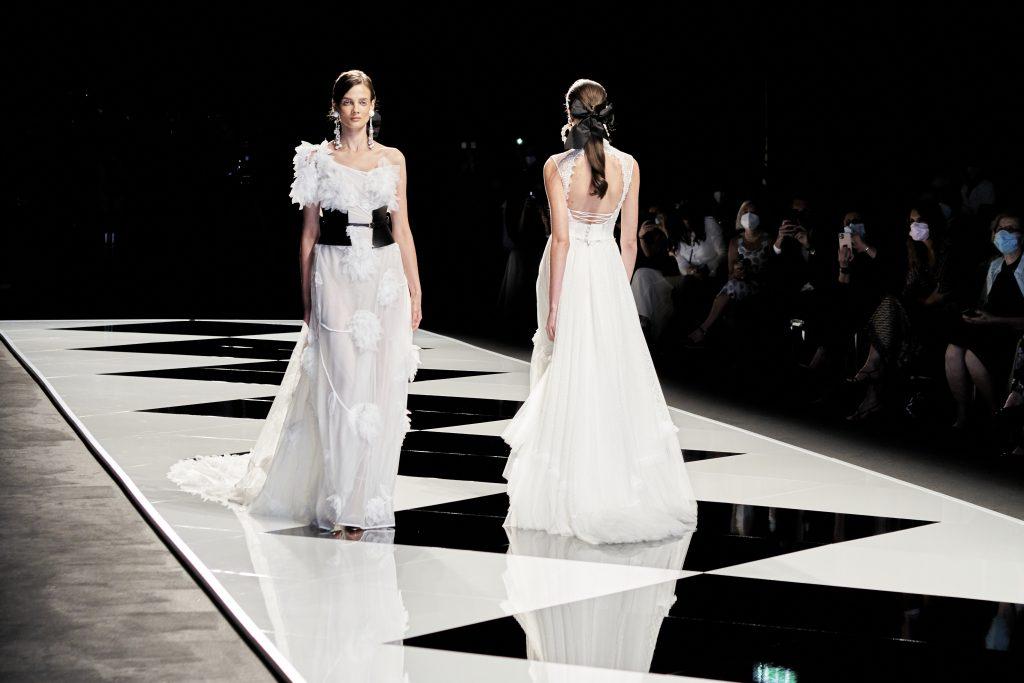 In questa immagine due abiti da sposa Elisabetta Polignano 2022 sfilano in passerella.