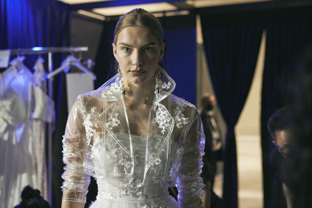 In questa foto una modella indossa il chiodo in plastica trasparente nel backstage della sfilata di abiti da sposa Elisabetta Polignano 2022
