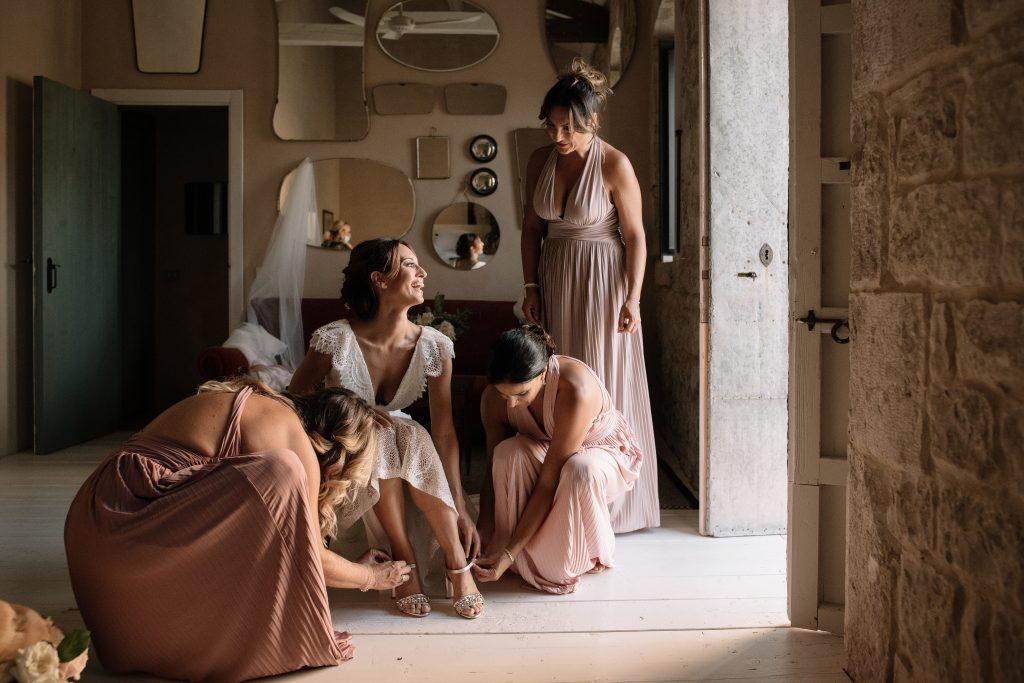 In questa foto di Primopiano Photografica di Rosa Lipari la sposa si sta vestendo insieme alle amiche