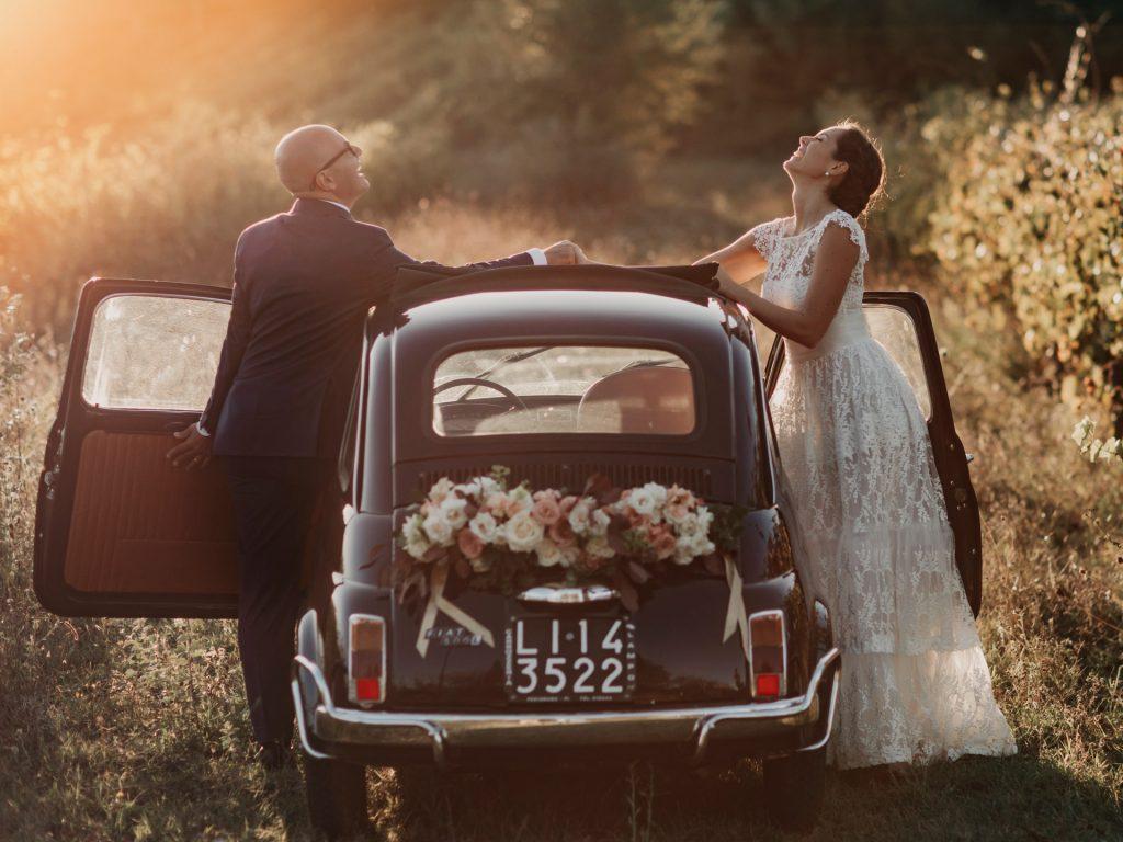 In questa foto di Studio fotografico Righi gli sposi posano divertiti davanti ad una Cinquecento antica