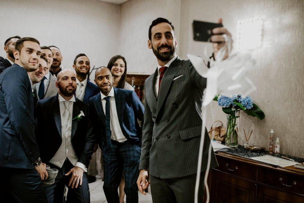In questa foto di Valerio Pantani photography il selfie dello sposo con un gruppo di amici