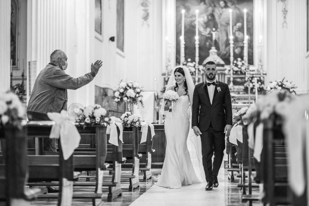 In questa foto di Vincenzo Aluia una coppia cammina lungo la navata e sorride ad un invitato