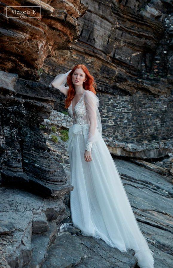 In questa foto una modella indossa un abito da sposa Victoria F 2022 di Maison Signore
