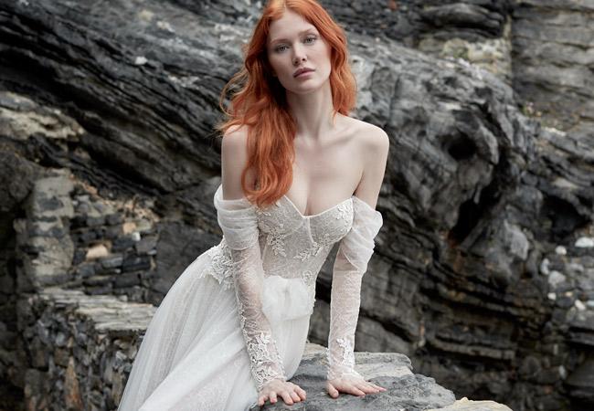 In questa foto una modella indossa un abito da sposa della collezione Victoria F 2022 di Maison Signore