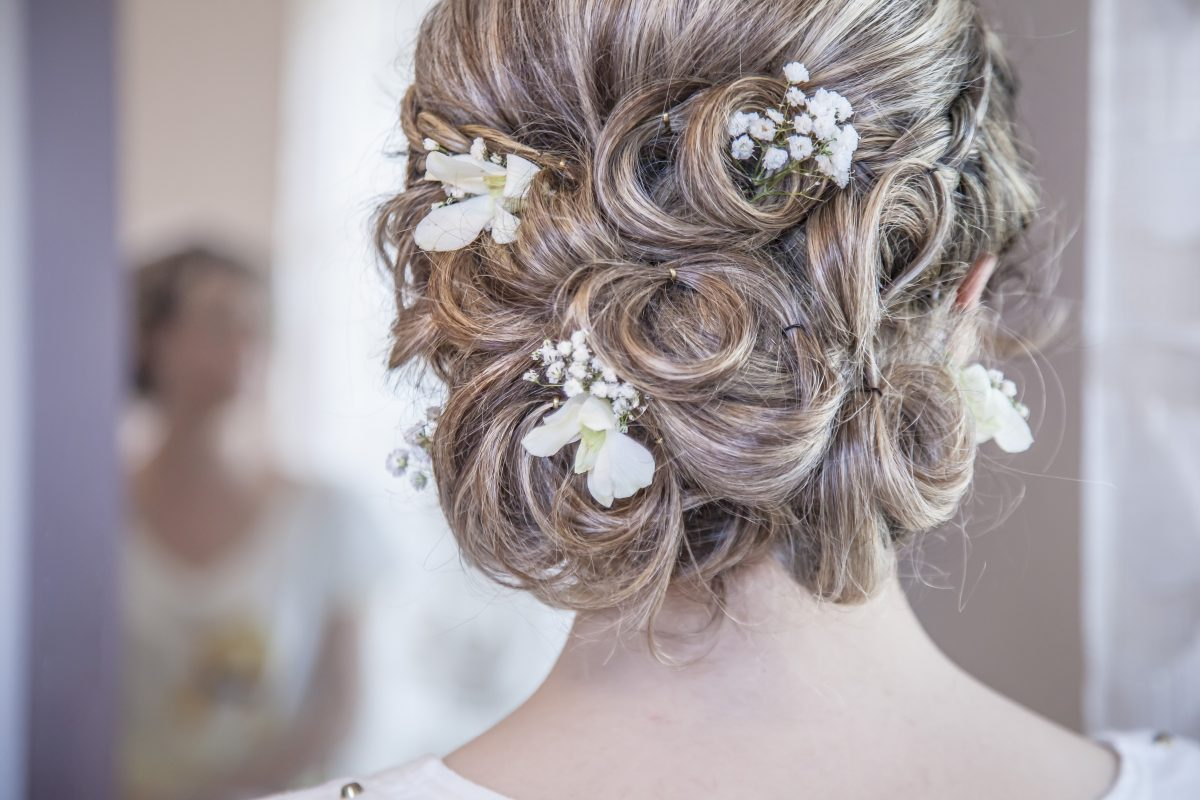In questa foto un'acconciatura raccolta arricchito da fiori bianchi in tessuto