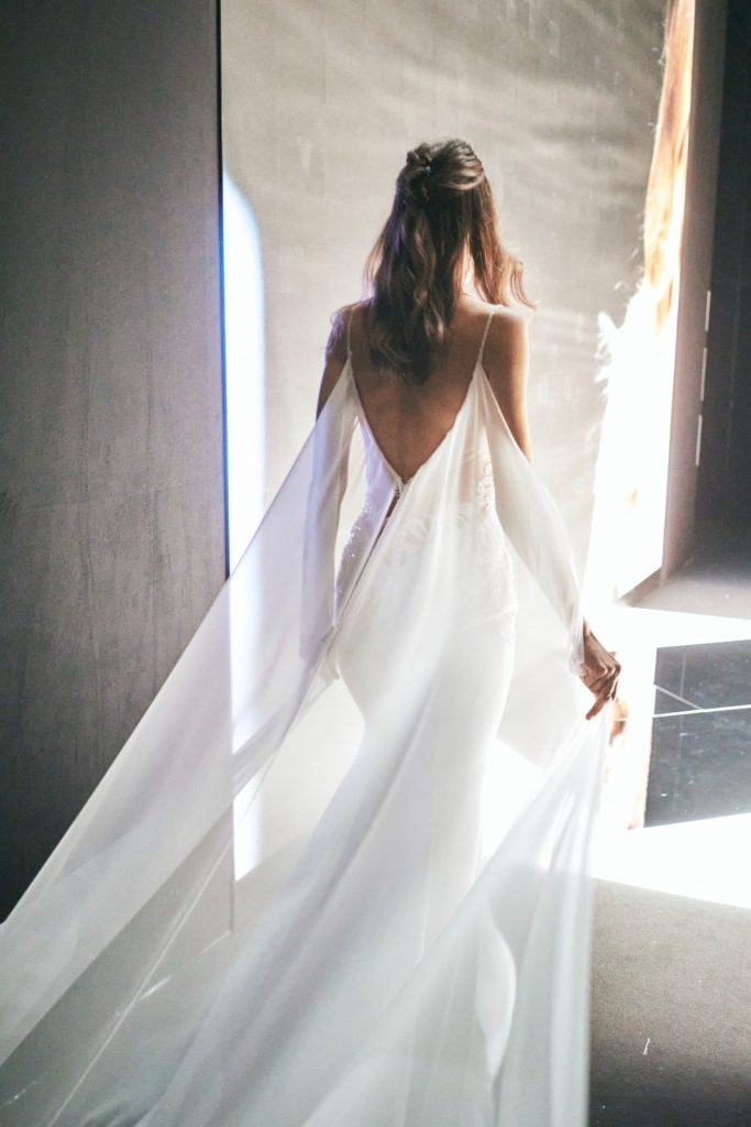 In questa foto un abito da sposa con lunghi veli che partono dalle spalle