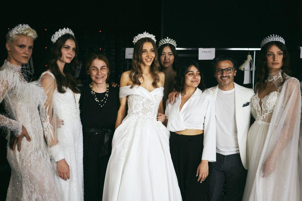 In questa foto modelle con cerchietti con pietre preziose posano sorridenti con Gino Signore, la moglie Vittoria Foraboschi e la giovane Camilla Elena.
