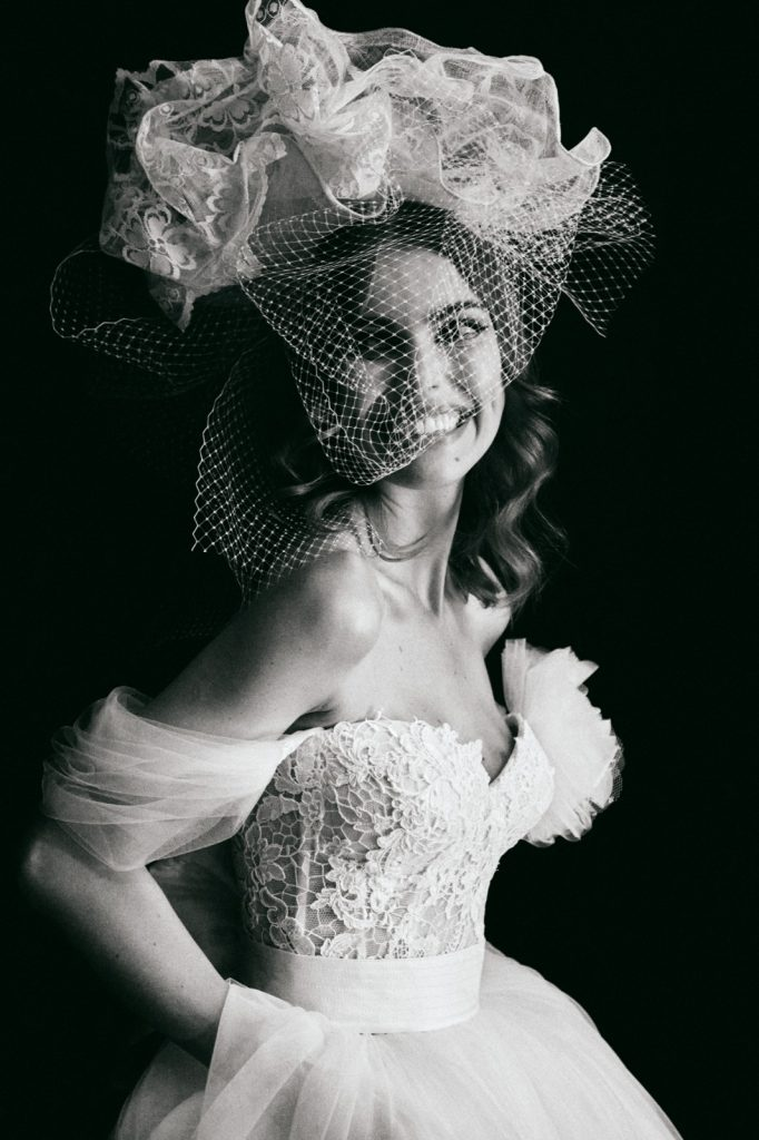 In questa foto una sposa con cappello e veletta, accessori di tendenza per il 2022