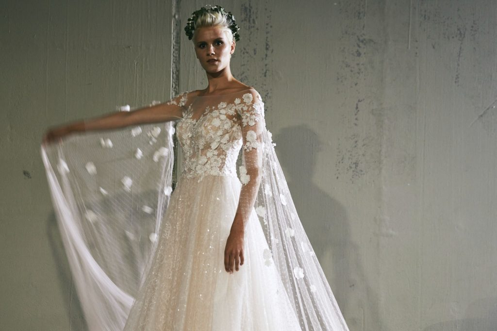 In questa foto un abito da sposa con lunghi veli con fiori in 3D che partono dalle maniche