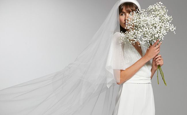 In questa foto una modella Max Mara Bridal che indossa un abito da sposa scivolato e un velo da sposa in tulle a taglio vivo. Guarda a sinistra tenendo davanti metà del volto un bouquet di fiori velo da sposa