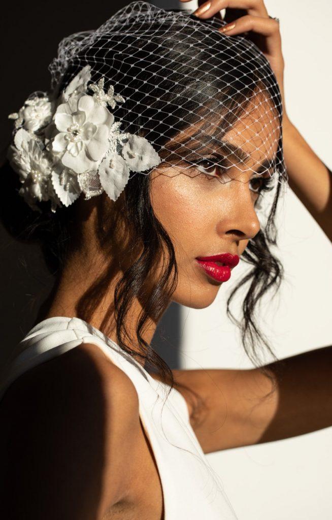 In questa foto una modella posa alla luce del tramonto con una veletta da sposa bianca in rete con fiori 3D sul lato destro