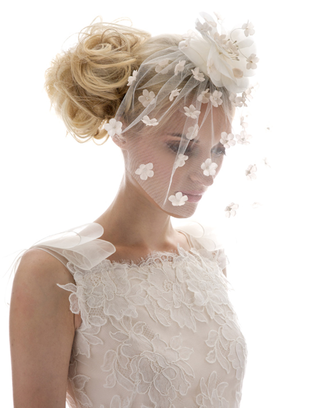 In questa foto una modella indossa un a veletta da sposa con fiori 3D ricamati su tutta la lunghezza e fermata sul capo da un fiori in stoffa più grande. Indossa un abito in macramè e porta uno chignon scombinato