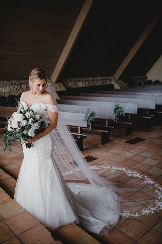 In questa foto una sposa all'interno di una cappella che guarda in basso mentre stringe il suo bouquet a braccio di fiori bianchi ed eucalipto. La sposa indossa un abito a mezza sirena e un velo Chiesa con pizzo rebrodè
