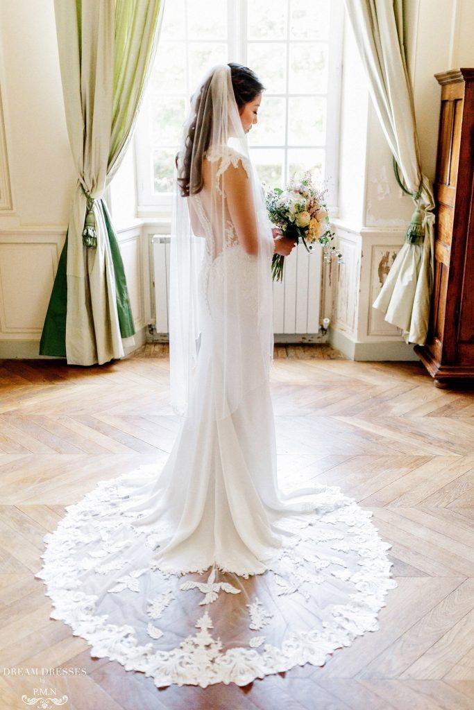 In questa foto una sposa è ritratta nella stanza di un antico palazzo mentre guarda il suo bouquet e indossa un velo Floor con bordo in pizzo Rebrodè  abbinato ad un abito a sirena con scollatura sulla schiena effetto tattoo