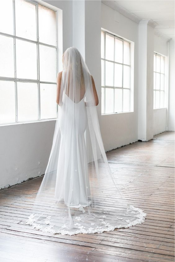 In questa foto una modella è ritratta di spalle in una stanza vuota mentre indossa un velo Floor con bordo in pizzo e un abito scivolato