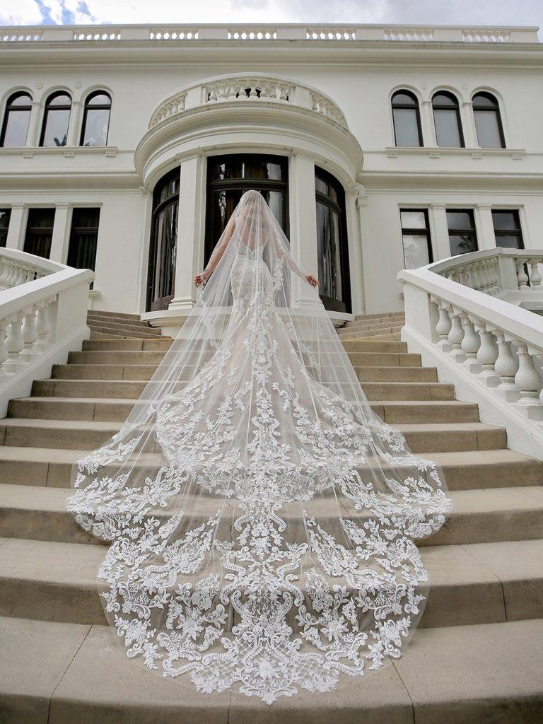 In questa foto una modella ritratta su una scalinata mentre indossa un abito a mezza sirena in pizzo rebrodato e un velo Royal abbinato tenuto aperto con le mani