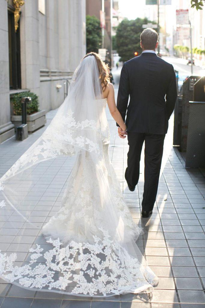 In questa foto due sposi che camminano per la strada visti di spalle. La sposa indossa un velo a cappella con pizzo rebrodè abbinato all'abito a mezza sirena