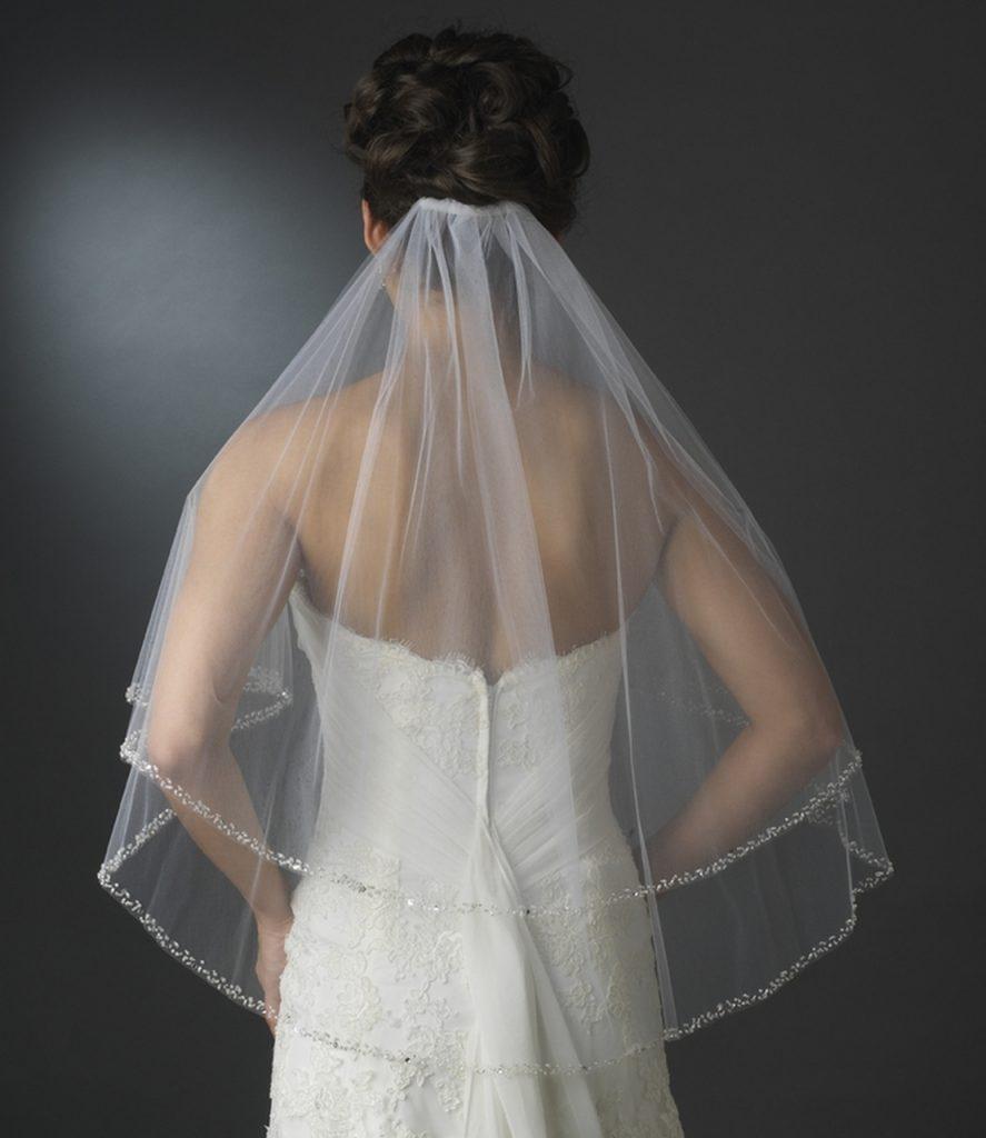 In questa foto una modella indossa un  velo da sposa a gomito su due lunghezze con bordo di perline fissato sotto uno chignon