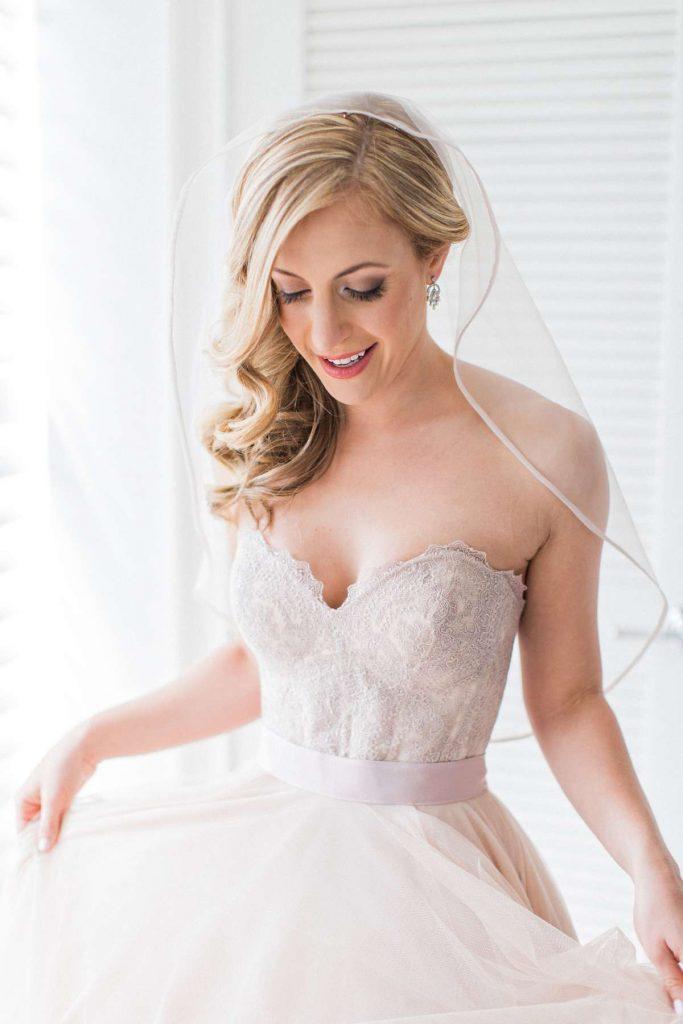 In questa foto una sposa guarda in basso e indossa un velo a gomito con bordo in raso fermato in cima alla testa. La sposa porta un'acconciatura raccolta su un lato e un abito con scollatura a cuore rosa cipria