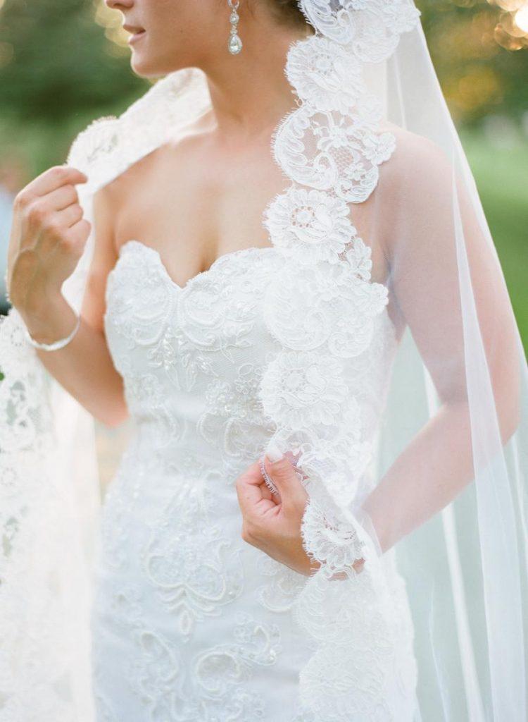 In questa foto il dettaglio di una sposa che indossa un abito a sirena con scollo a cuore decorato con perline e ricami 3D abbinato ad un velo da sposa a mantiglia